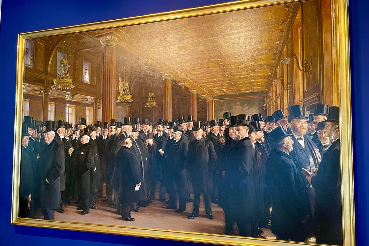 """Efter en omfattende og langvarig restaurering af P.S. Krøyers """"Fra Københavns Børs"""", er maleriet nu tilbage på sin plads i Biblioteket på Børsen. Specialdesignet lys-konstruktion kan yde billedet værdighed på alle timer af døgnet og i skiftende årstider."""